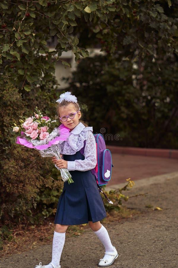 Uma criança da menina na farda da escola com curvas, vidros e um saco de escola no seu para trás vai à primeira classe da escola  fotografia de stock