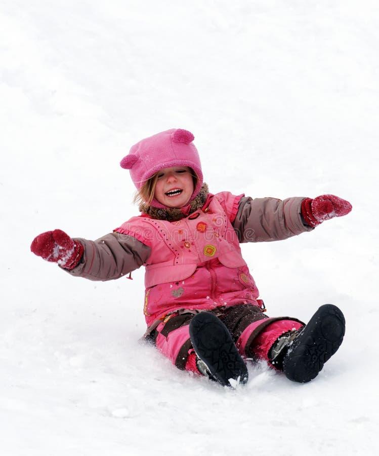 Uma criança de riso que desliza na neve fotografia de stock royalty free