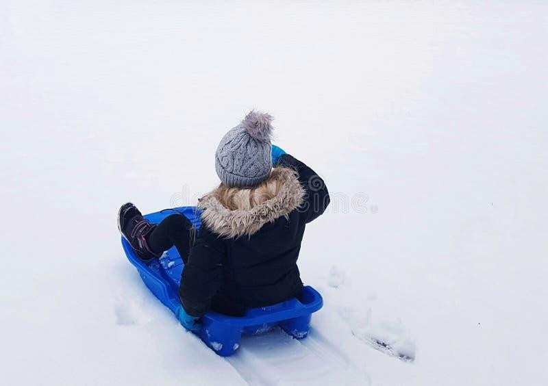 Uma criança em um pequeno trenó azul no inverno imagens de stock