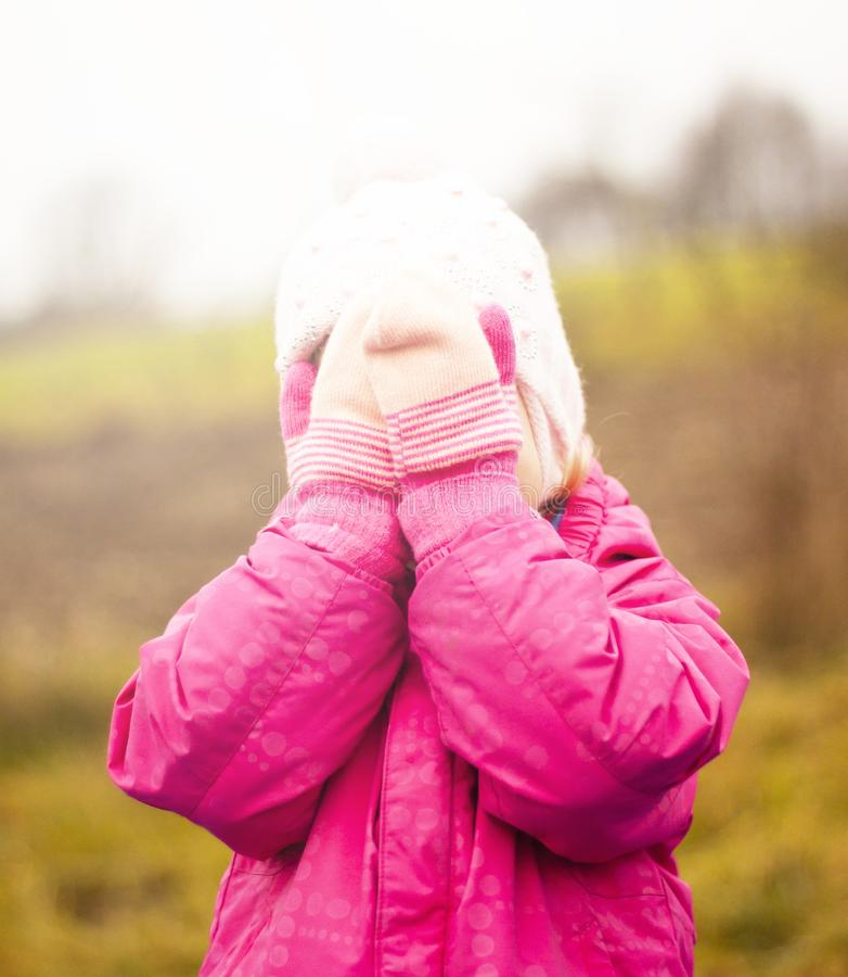 Uma criança em um revestimento vermelho e em um chapéu do branco joga o esconde-esconde na rua outono A cara é coberta com os mit imagens de stock