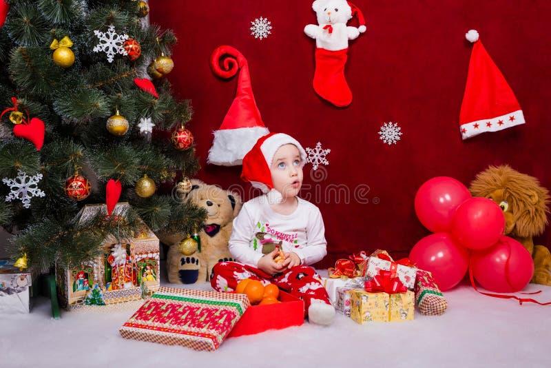 Uma criança encantador foi surpreendida receber presentes de Natal fotos de stock royalty free