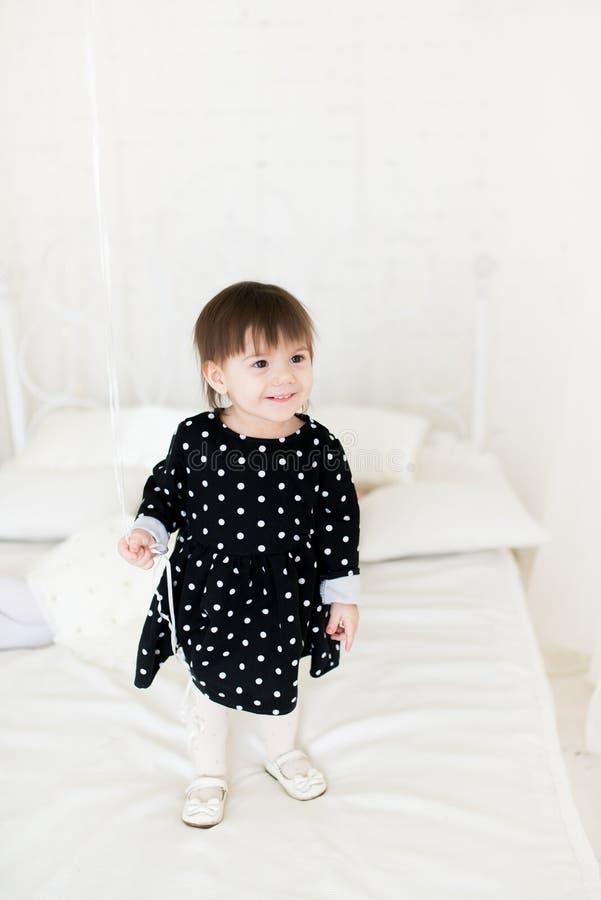Uma criança engraçada de 2 anos velho em um vestido do às bolinhas no crescimento completo está estando em uma cama em uma sala e foto de stock royalty free