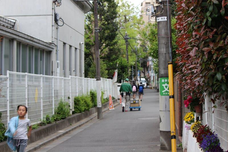 Uma criança está correndo da escola na rua em Japão fotografia de stock