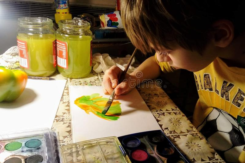 Uma criança está tirando uma pimenta do verde e de sino amarelo com uma pintura na noite imagem de stock royalty free