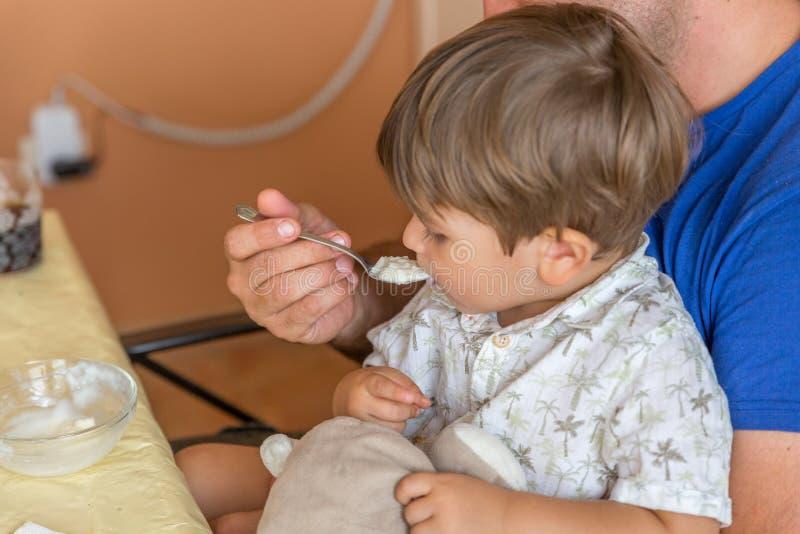 Uma criança macia come o arroz com leite que seu pai lhe dá, em uma reunião de família foto de stock