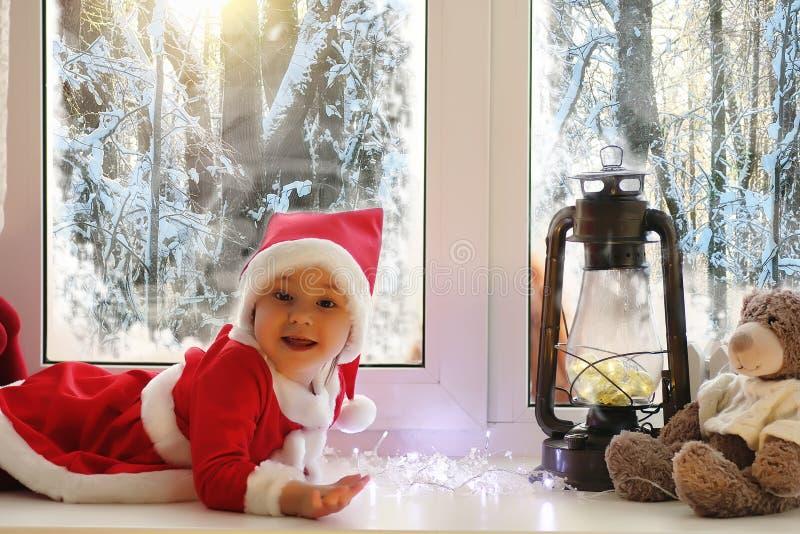 Uma criança no ano novo olha para fora a janela As crianças são waiti imagens de stock