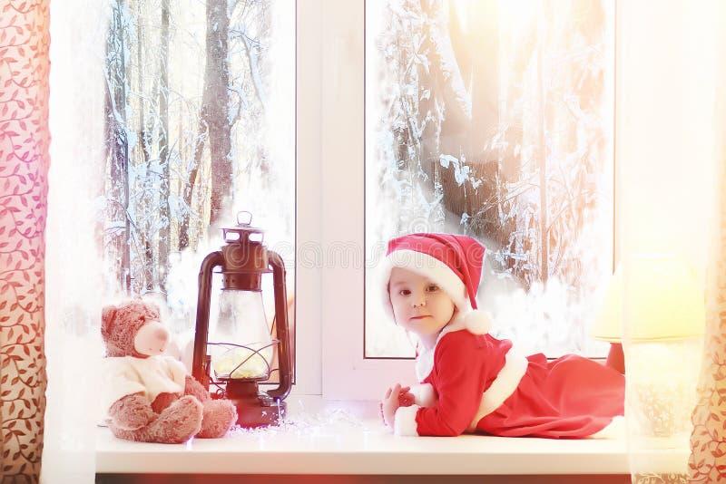 Uma criança no ano novo olha para fora a janela As crianças são waiti imagem de stock royalty free