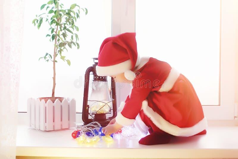 Uma criança no ano novo olha para fora a janela As crianças são waiti fotos de stock