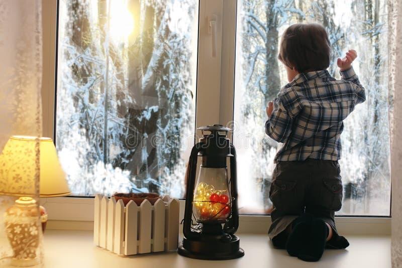 Uma criança no ano novo olha para fora a janela As crianças são waiti foto de stock royalty free