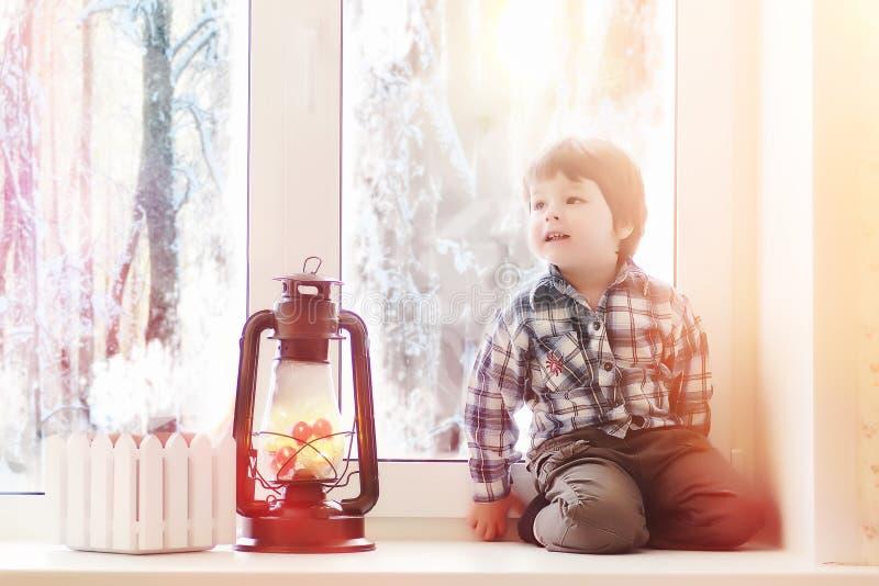 Uma criança no ano novo olha para fora a janela As crianças são waiti fotografia de stock