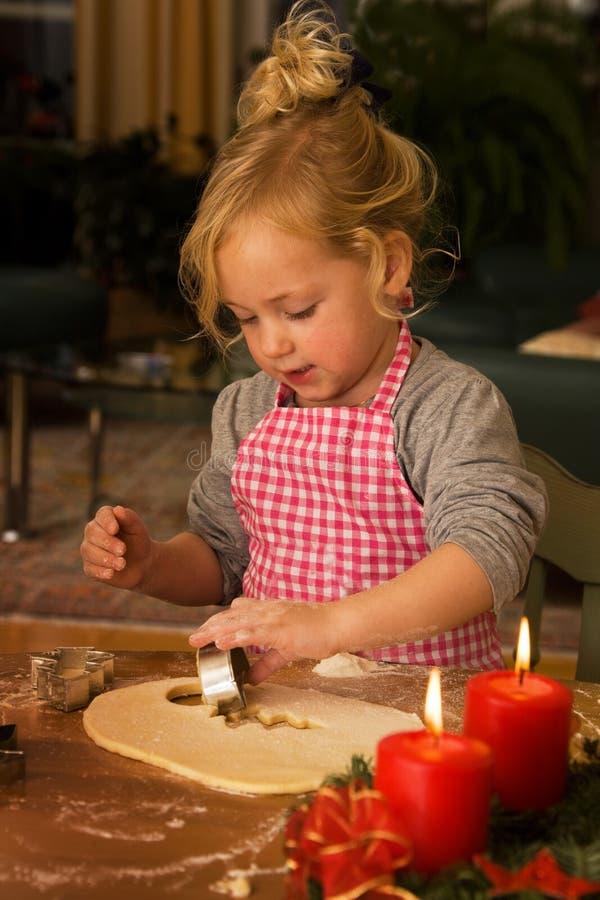 Uma criança no Natal no advento ao cozer bolinhos fotos de stock royalty free