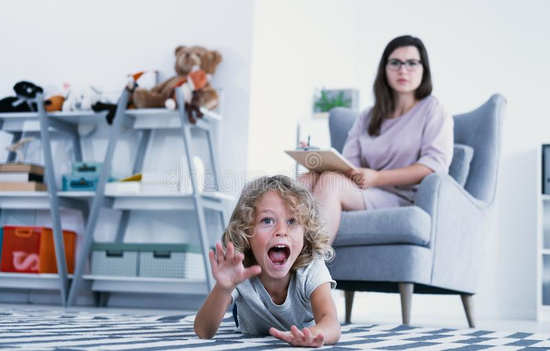 Uma criança overactive que grita e que bate um assoalho quando um psychotherapist fizer um diagnóstico durante uma reunião em um  imagem de stock