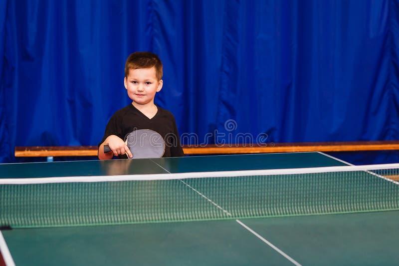 Uma criança pequena aprende jogar o tênis de mesa foto de stock royalty free