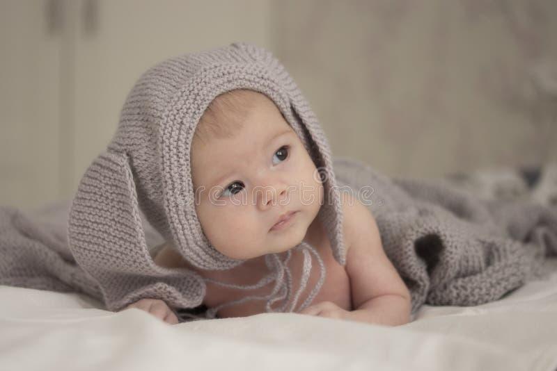 Uma criança pequena de 1 mês em um chapéu cinzento com orelhas olha ao lado Foco macio da luz suave imagens de stock royalty free