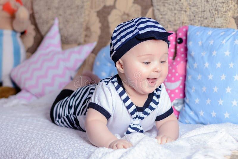 Uma criança pequena doce em uma camisa listrada e nos chapéus que encontram-se no sofá na sala fotografia de stock royalty free