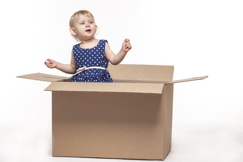 Uma criança pequena em umas caixas de cartão imagem de stock