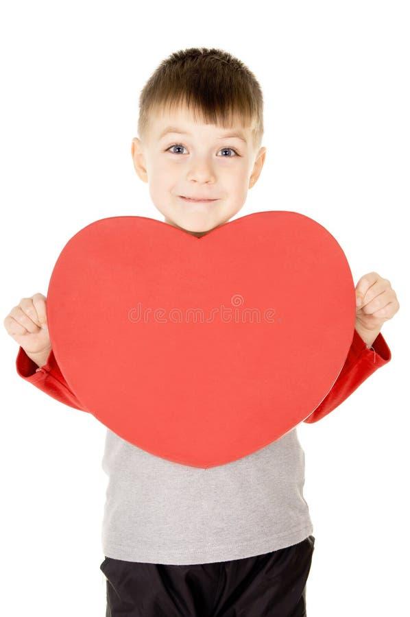Uma criança pequena está e guardara o coração imagem de stock