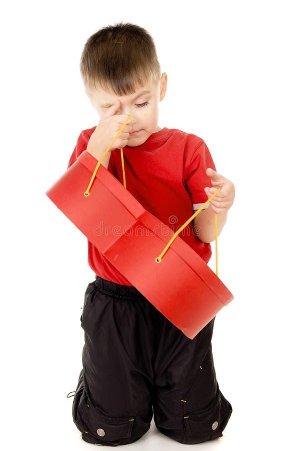 Uma criança pequena está guardarando uma caixa sob a fôrma do coração fotos de stock