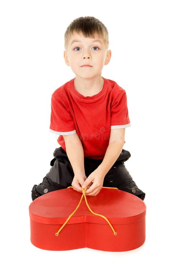 Uma criança pequena está guardarando uma caixa sob a forma do coração fotografia de stock