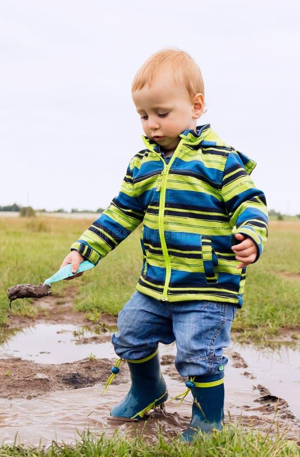 Uma criança pequena está jogando em uma poça enlameada fotografia de stock