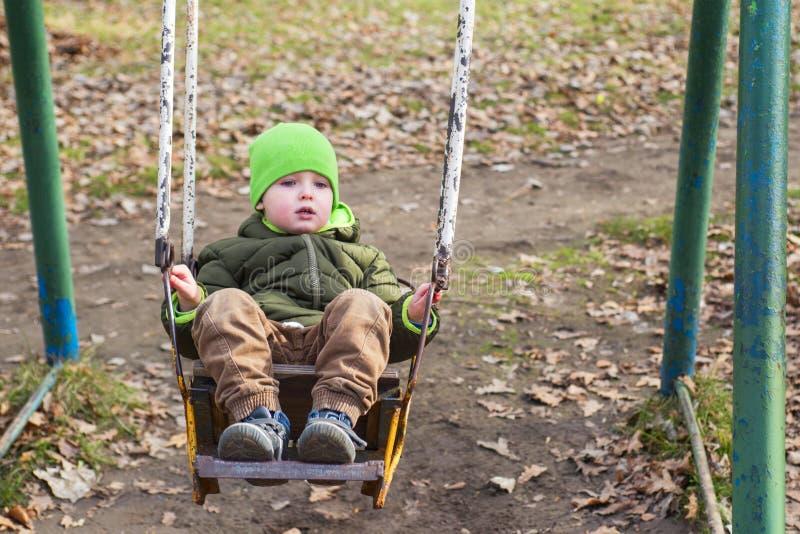 Uma criança pequena está montando em um balanço no parque no outono fotografia de stock royalty free