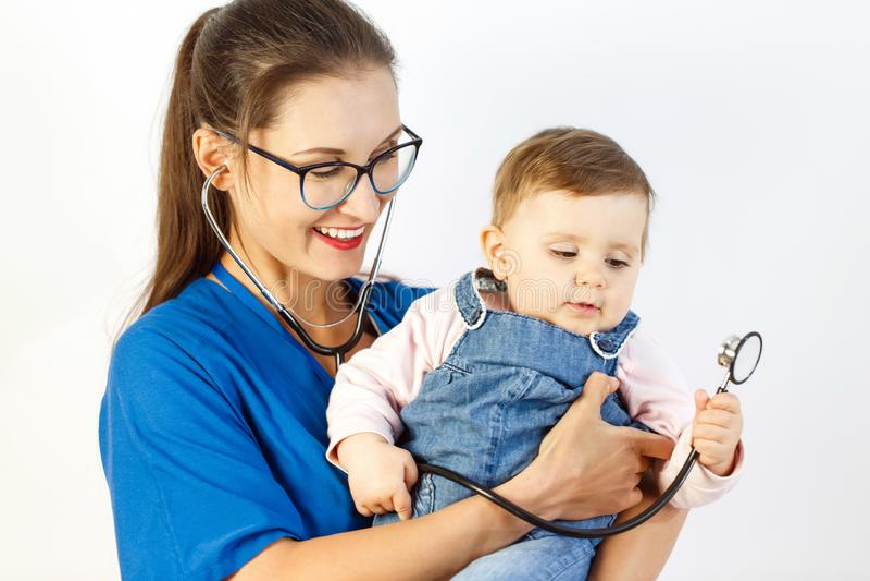 Uma criança pequena está olhando um estetoscópio que senta-se nas mãos de um doutor da jovem mulher imagens de stock royalty free
