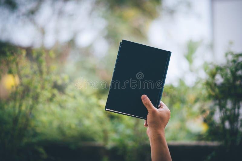 Uma criança pequena expressou a alegria ao receber uma caixa de presente Ao guardar um caderno e ao sustentá-lo imagem de stock