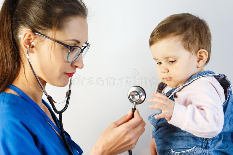 Uma criança pequena no exame no doutor olha o estetoscópio e puxa-lhe sua mão para imagens de stock