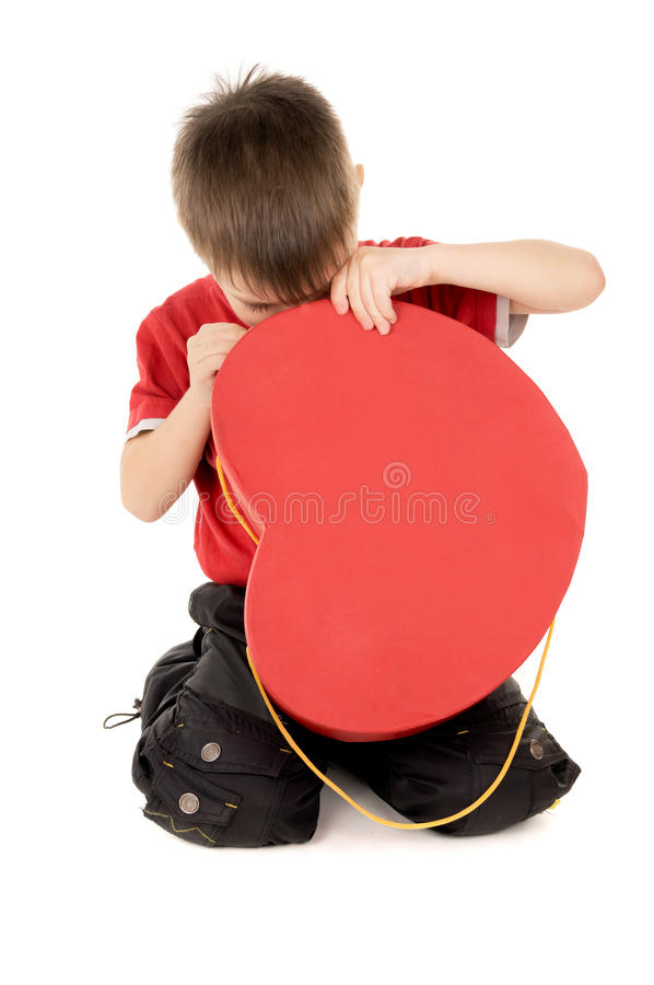 Uma criança pequena olha a caixa de cartão, sob a forma do coração fotos de stock royalty free