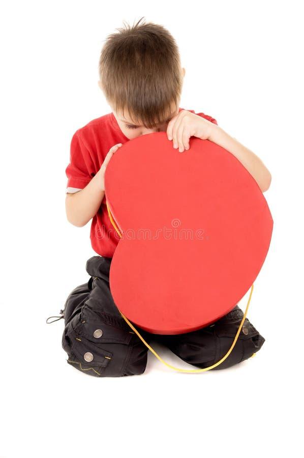 Uma criança pequena olha a caixa de cartão, sob a forma do coração imagens de stock royalty free
