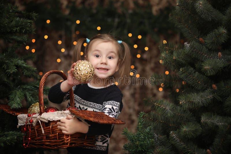 Uma criança pequena pela árvore do ano novo As crianças decoram o Chris fotografia de stock royalty free