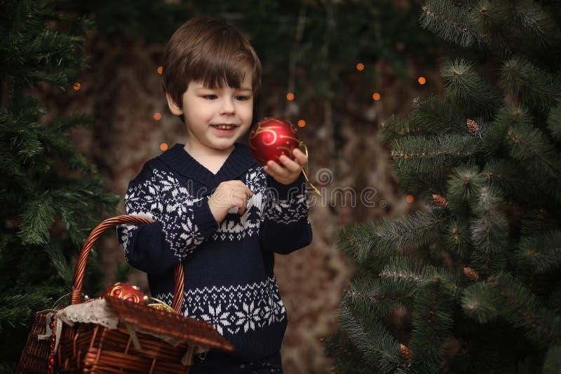 Uma criança pequena pela árvore do ano novo As crianças decoram o Chris imagens de stock