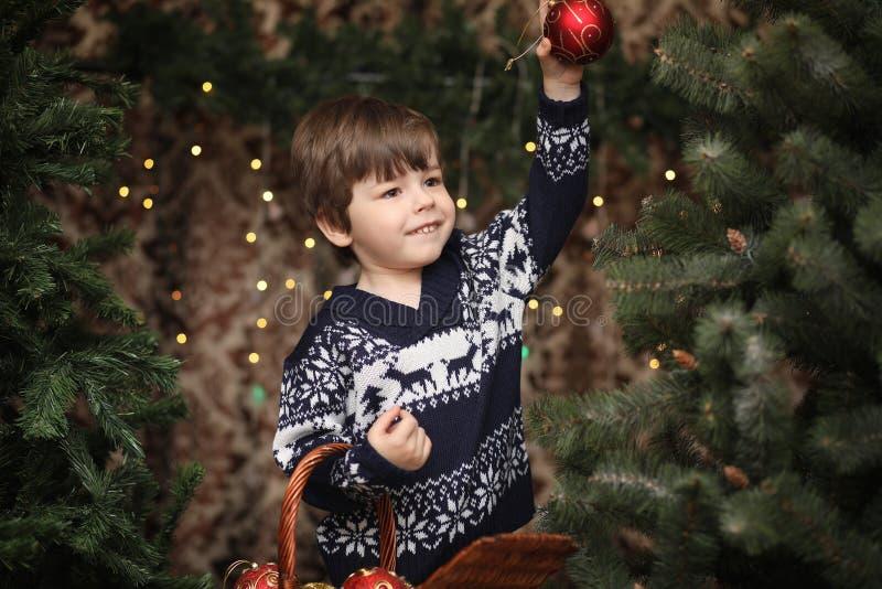 Uma criança pequena pela árvore do ano novo As crianças decoram o Chris imagem de stock
