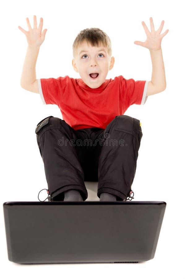 Uma criança pequena que olha feliz no computador portátil, aumento foto de stock