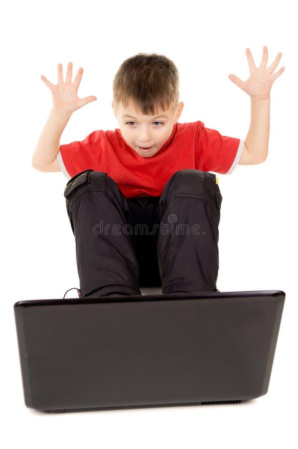 Uma criança pequena que olha felizmente no laptop, aumento foto de stock royalty free