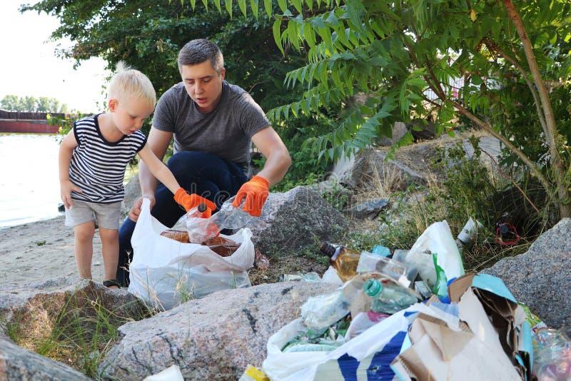 Uma criança pequena recolhe o lixo na praia Seu paizinho aponta seu dedo onde jogar o lixo Os pais ensinam a crianças a limpeza foto de stock