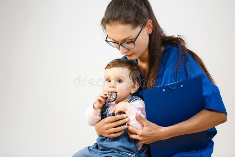 Uma criança pequena senta-se nas mãos de um doutor e joga-se com um estetoscópio foto de stock royalty free