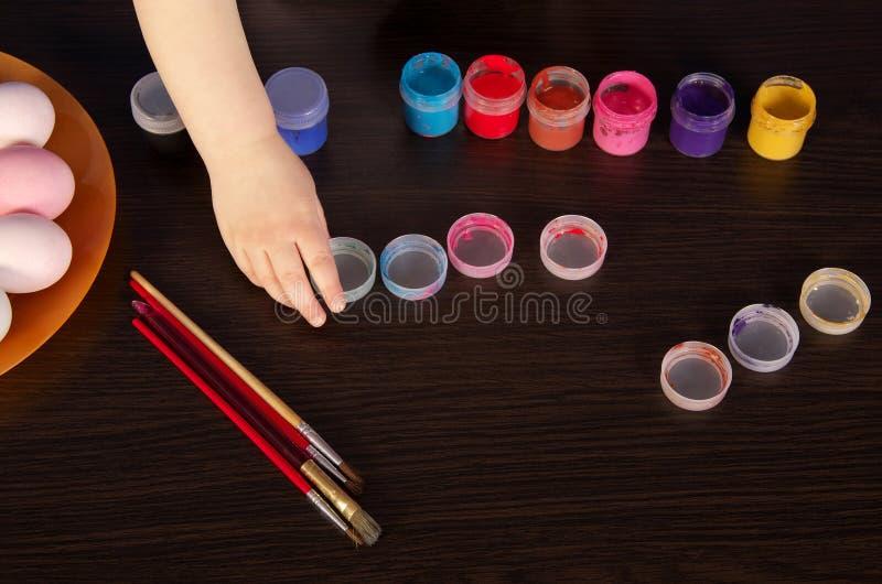 Uma criança pinta ovos da páscoa mão, pincel e pintura na tabela Preparação para Easter fotos de stock