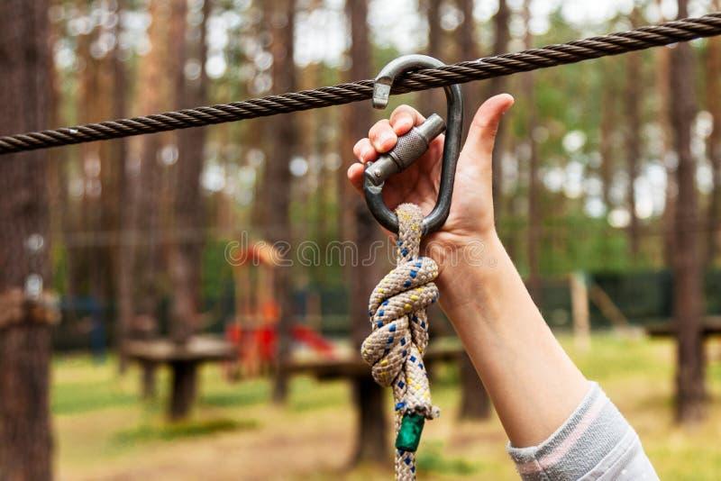 Uma criança prende uma carabina em uma corda da segurança foto de stock