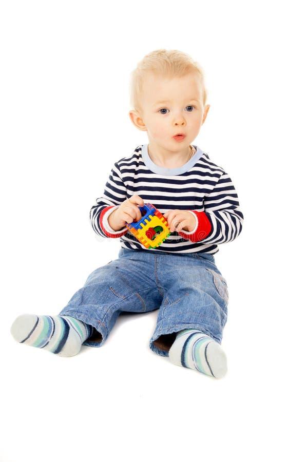 Uma criança que joga com um brinquedo imagem de stock royalty free