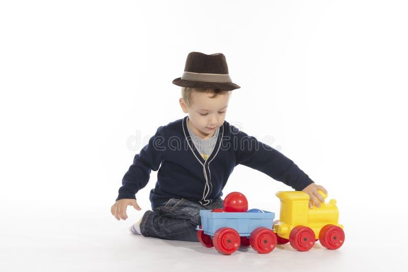 Uma criança que joga com um brinquedo do trem imagem de stock royalty free