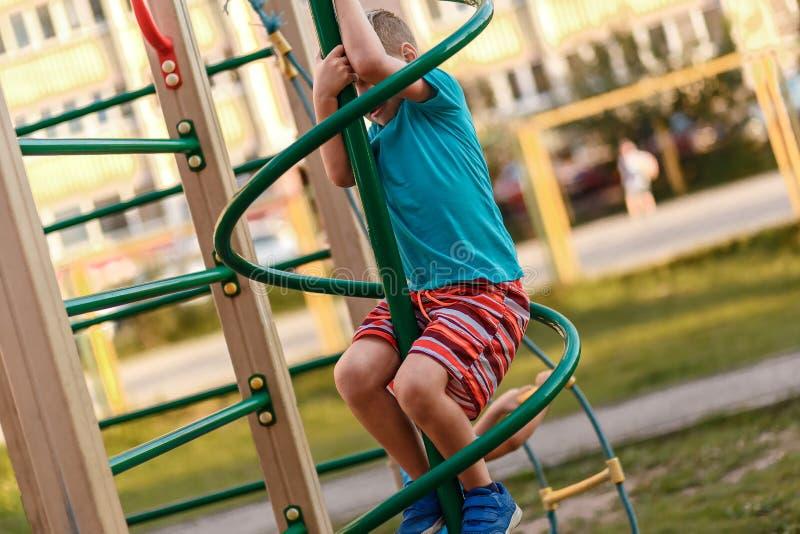 Uma criança que joga no campo de jogos perto da casa no verão fotos de stock royalty free