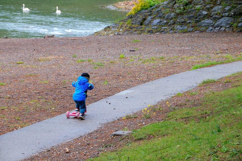 Uma criança que monta seu 'trotinette' cor-de-rosa em uma passagem da praia foto de stock