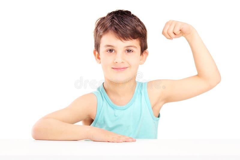 Uma criança que mostra seus músculos assentados em uma tabela imagem de stock