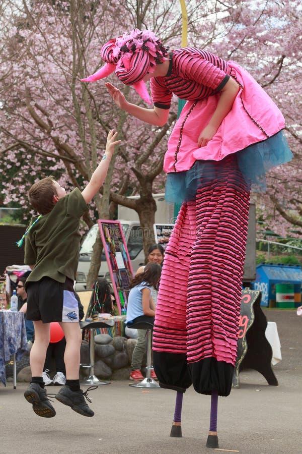 Uma criança salta para dar um alto-cinco a um caminhante do pernas de pau fotografia de stock royalty free