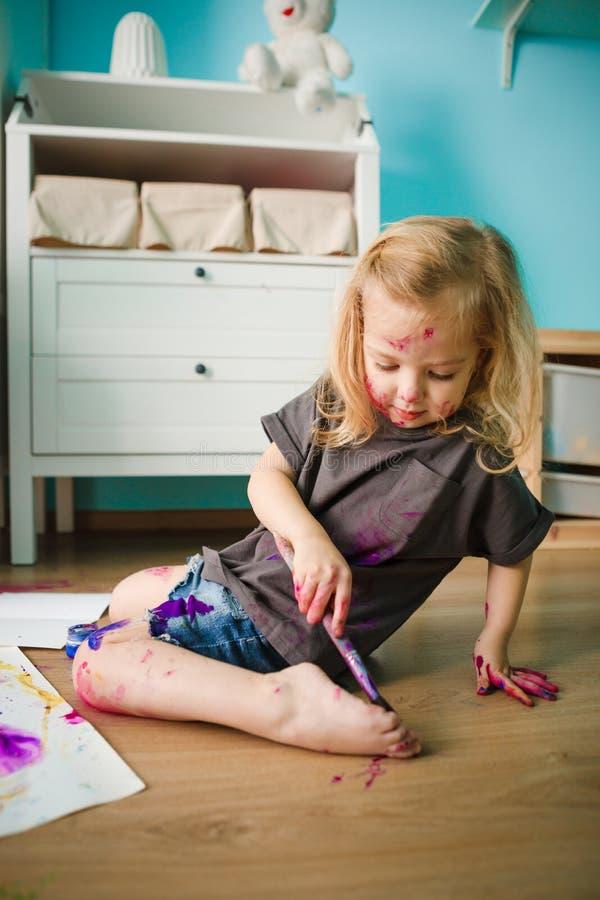 Uma criança se desenha sobre um cavalete com tintas sentada no chão do quarto de uma criança foto de stock