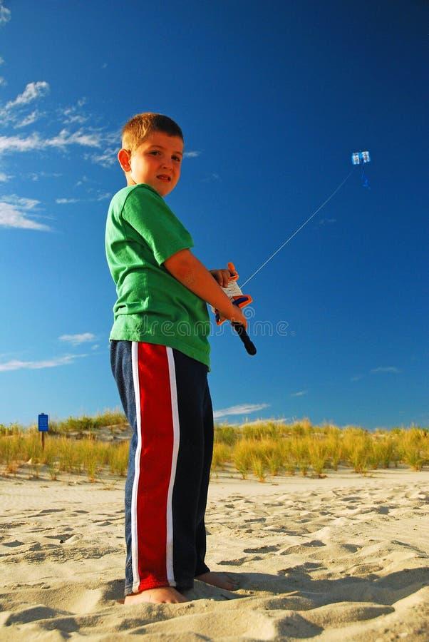Uma criança voando pipa no dia do verão imagem de stock