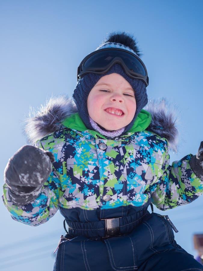 Uma crian?a pequena que joga no parque do inverno Beb? de jogo e de sorriso no fundo azul Resto e jogos ativos fotos de stock royalty free
