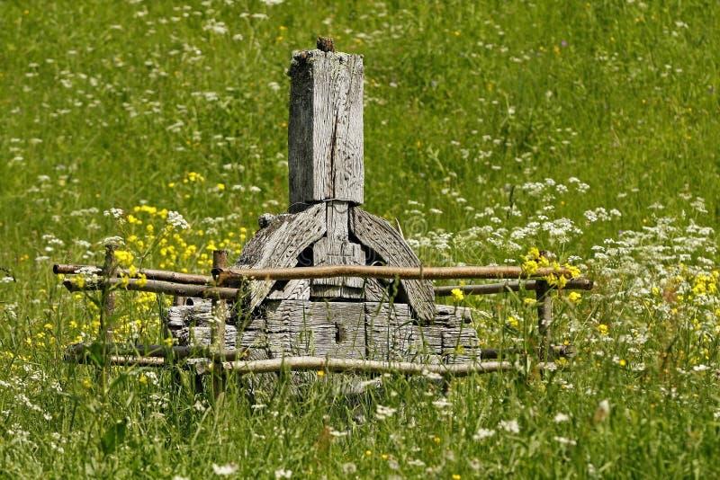 Uma cruz celta de madeira velha em um prado verde imagem de stock