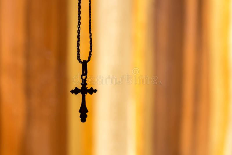 Uma cruz em uma corrente em um fundo alaranjado fotografia de stock royalty free